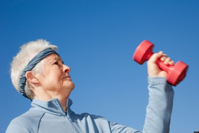 Britain, UK, Europe. Grey haired senior woman pensioner exercising with dumbbell hand weights to keep healthy